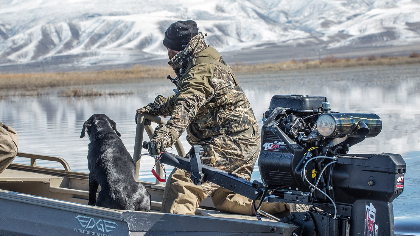 Hunter with dog boating on icy lake.