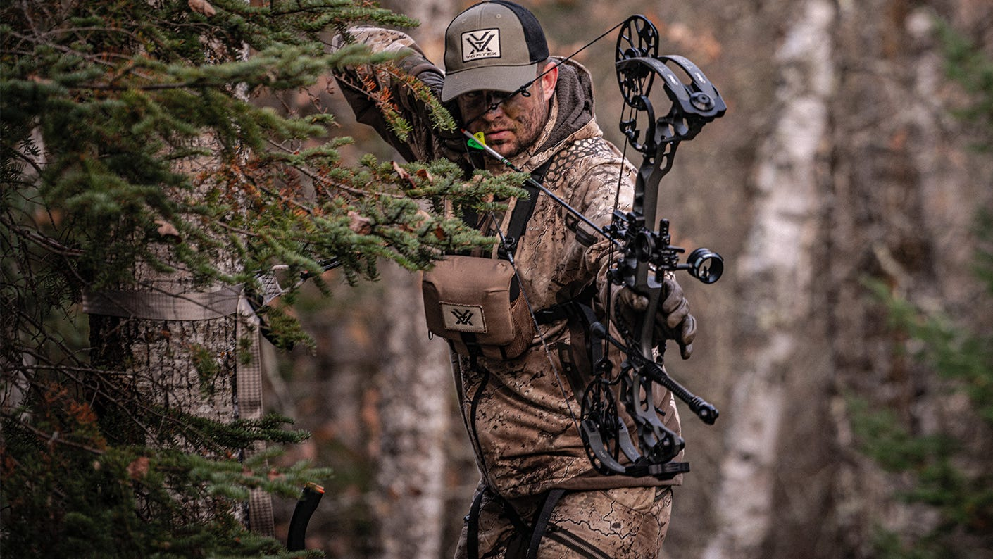 Bow hunter standing in tree stand aiming bow.