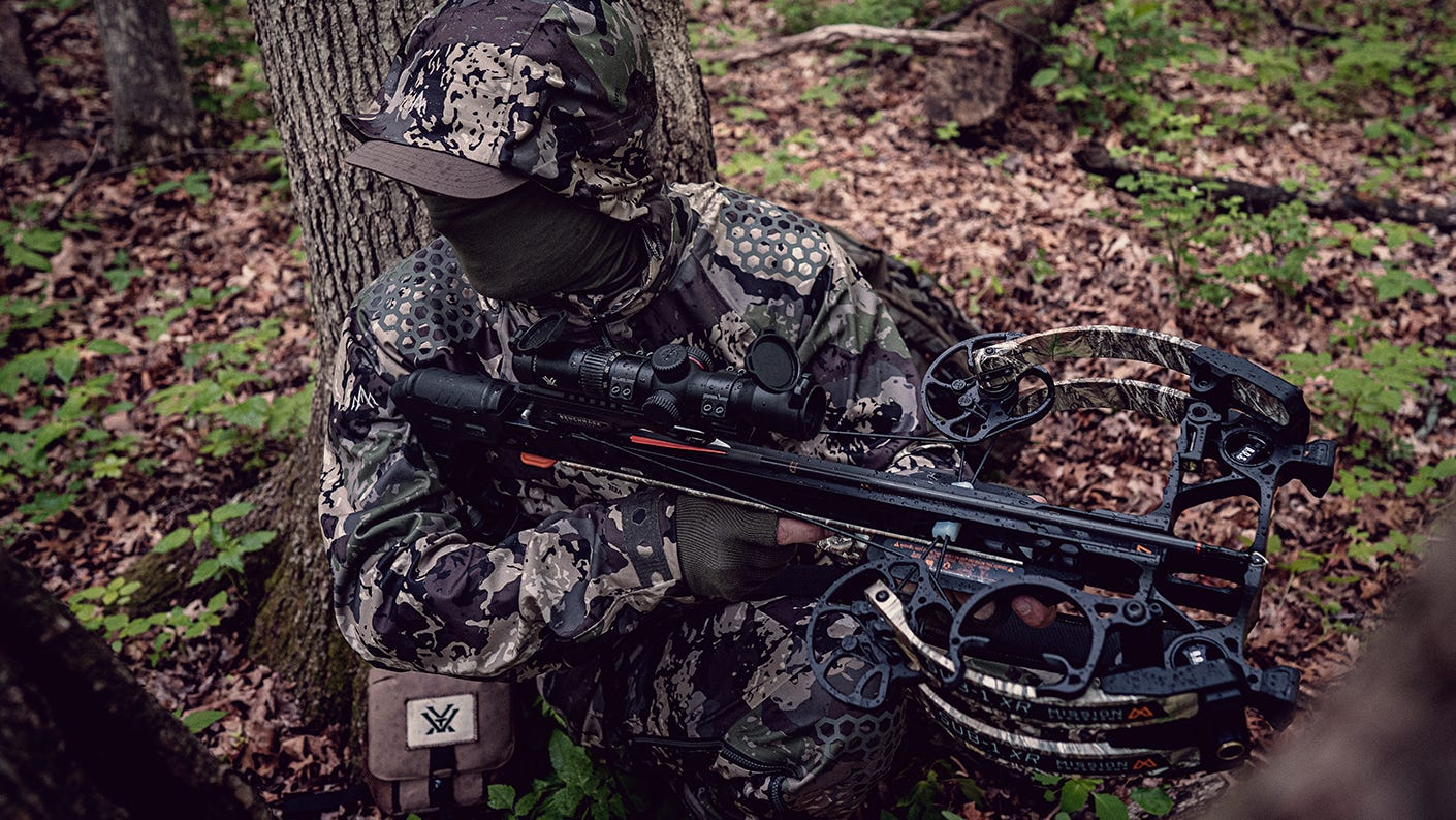 Bow hunter setting against tree scouting for deer.