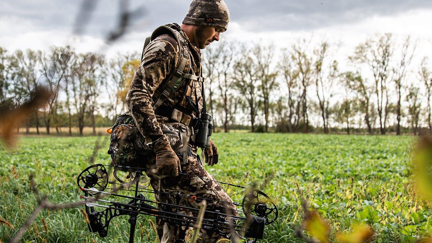 Bow Hunter Walking In Field