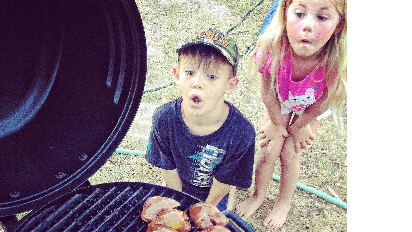 Kids looking at seasoned dove breasts in the process of grilling.