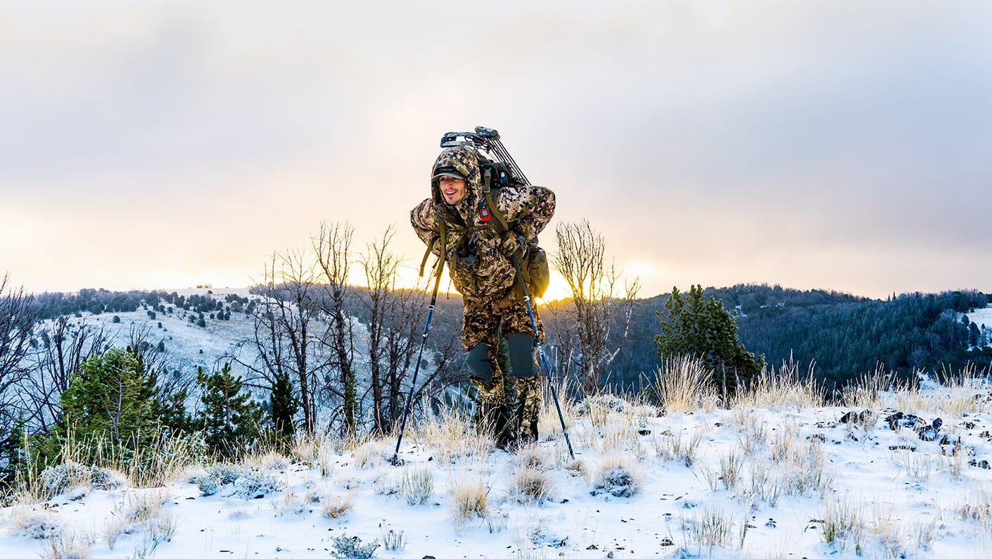 Elk hunter hiking in snow covered mountains.