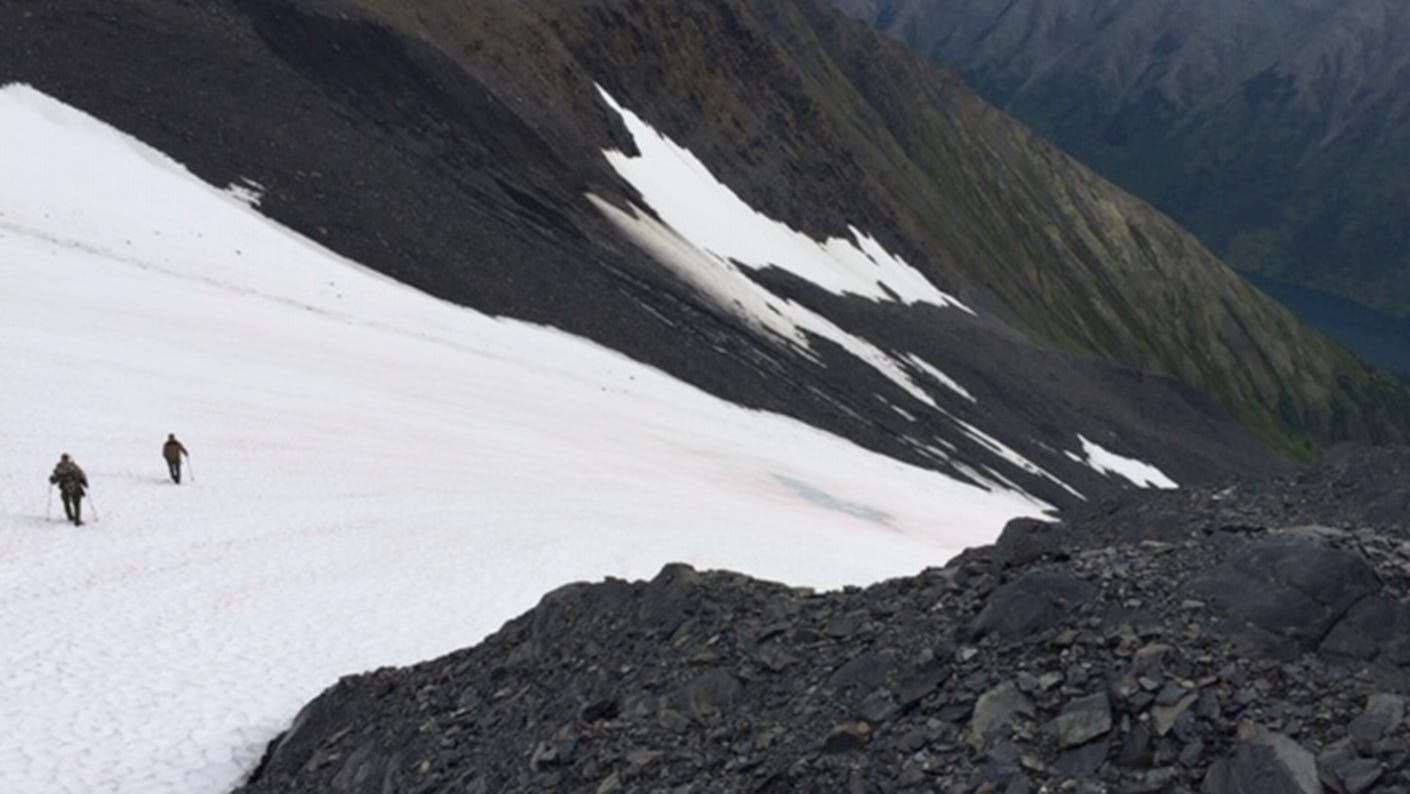 Hunter and guide climbing a glacier in Alaska.