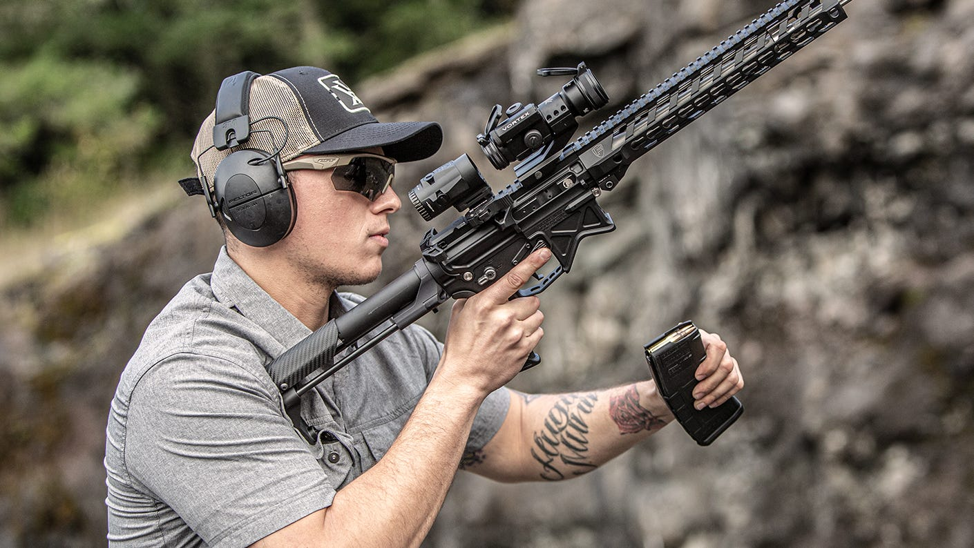 Shooter loading his weapon at an outdoor shooting range.
