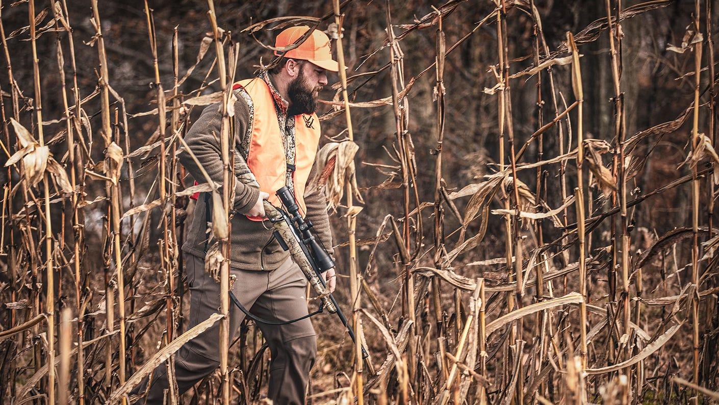 Mid-western hunter walking through a corn field with the Crossfire II Straight-Wall riflescope.