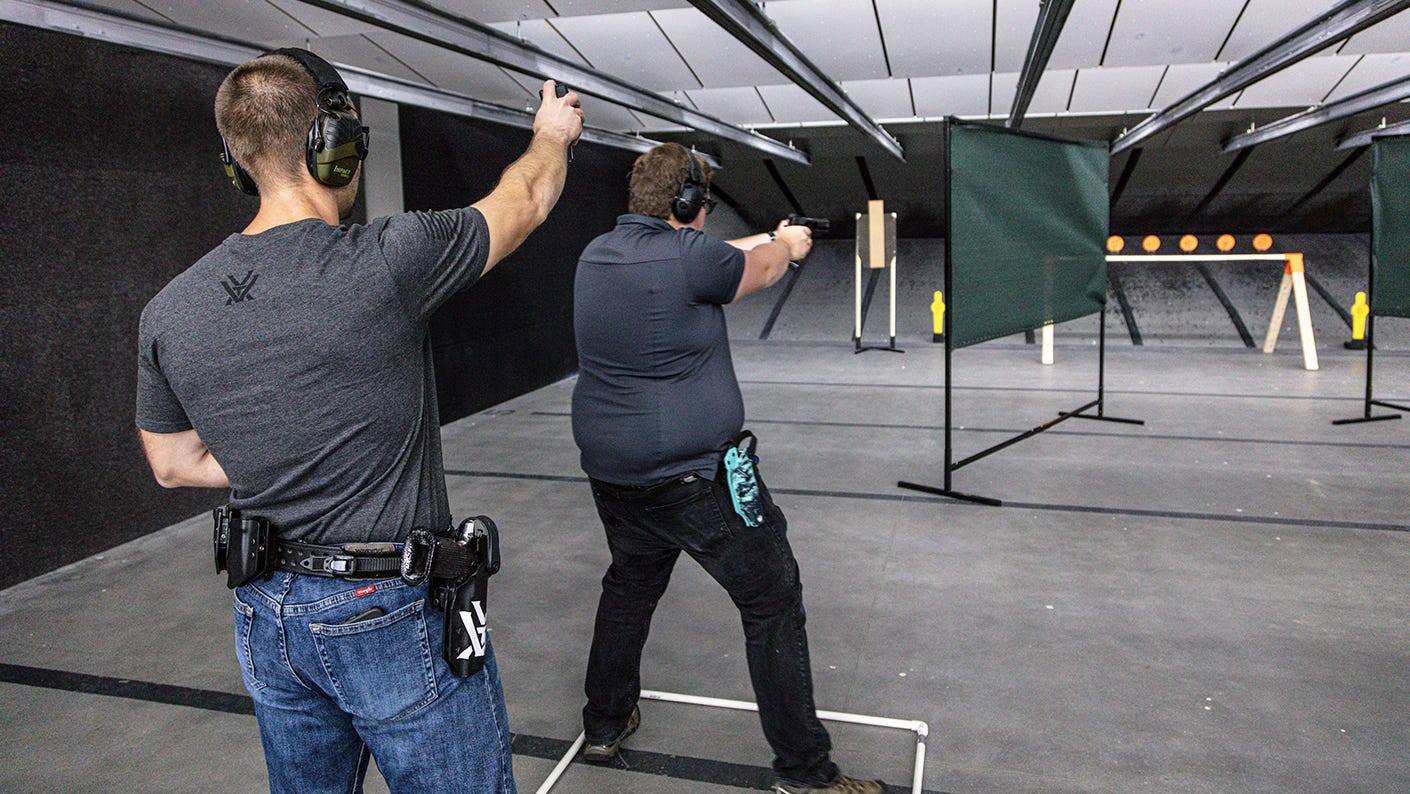 Action pistol training with instructor using a timer.
