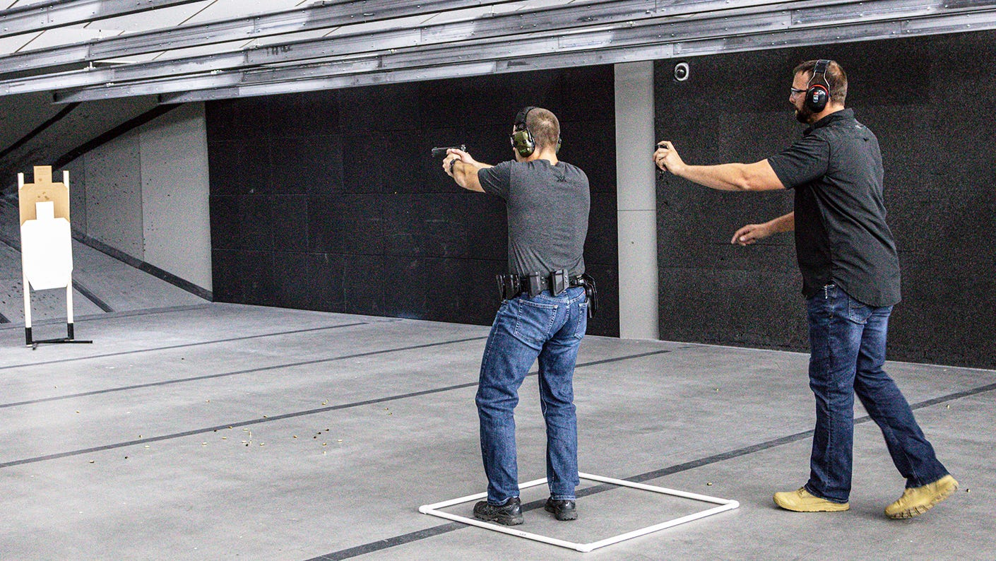 Action pistol training in an indoor range with instructor.